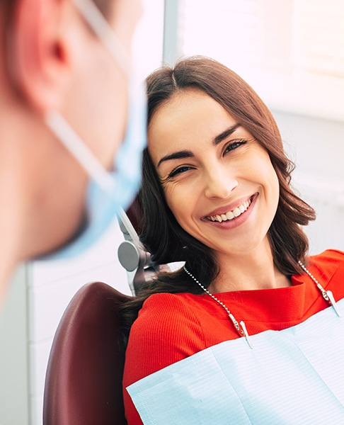 Woman in dental chair laughing with dentist