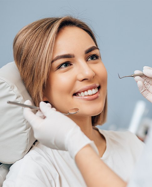Woman smiling during preventive dentistry checkup and teeth cleaning visit
